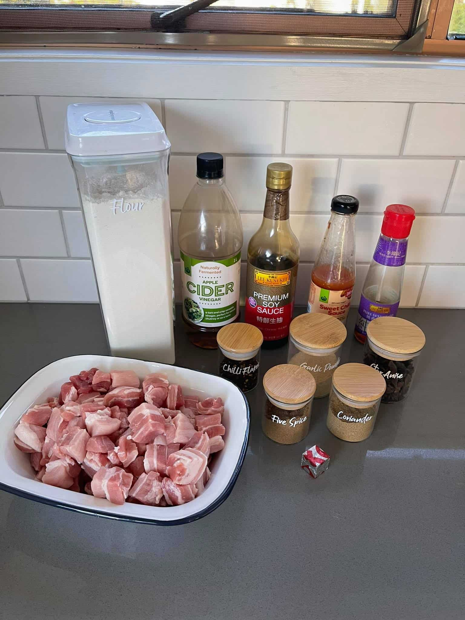 Diced pork in a white dish, a container of flour, sauce bottles and spice jars sitting on a grey bench.