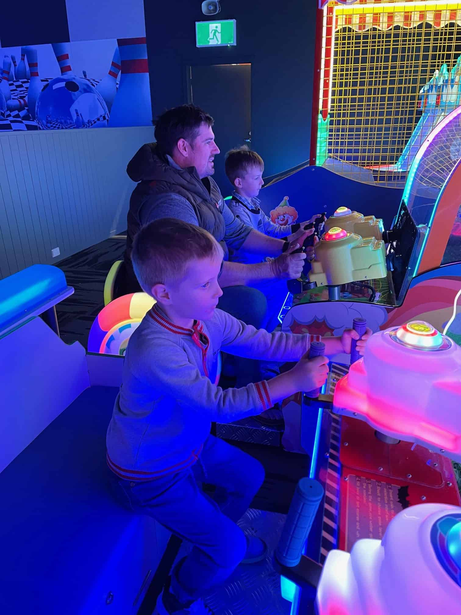 Father and sons playing arcade games.
