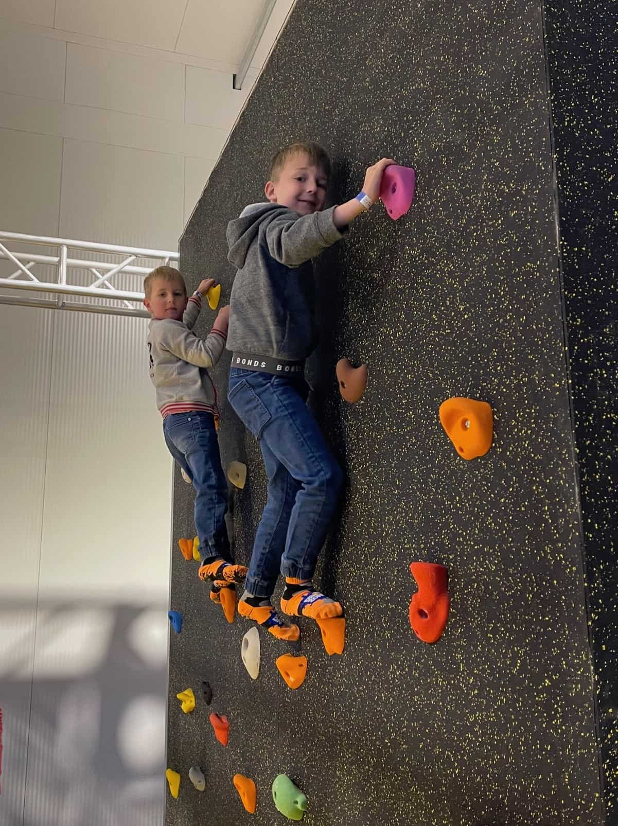 Two boys on a climbing wall.