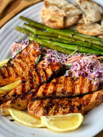 pesto salmon on a plate with slaw and pita pockets