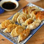 Pork and Ginger Dumplings on a blue plate with soy sauce