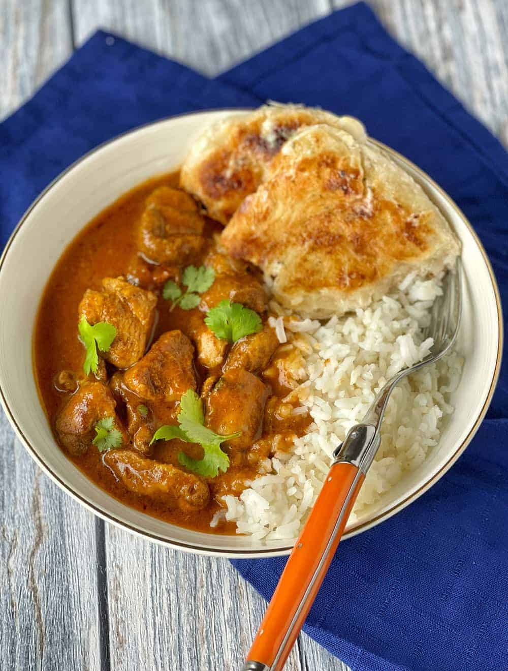 Butter chicken, rice, coriander and roti in a white bowl with an orange fork.