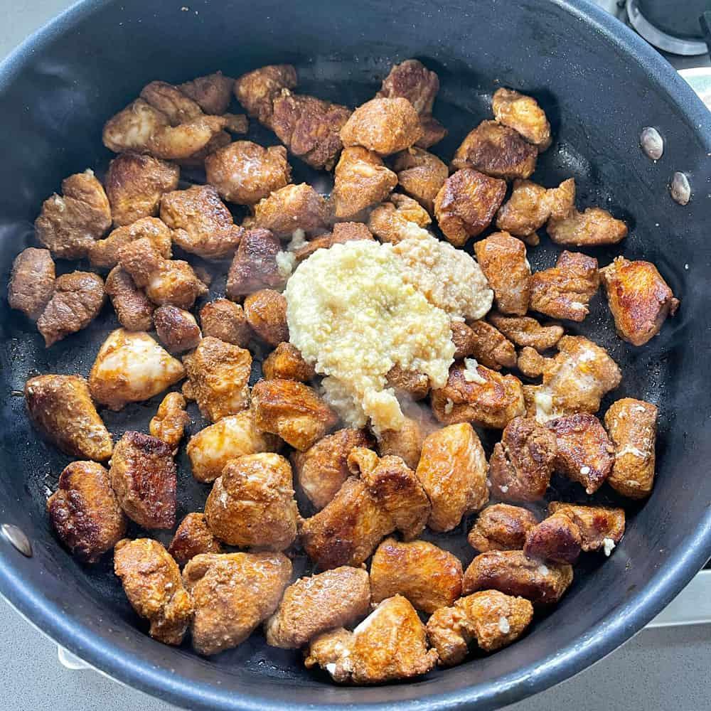 Spiced, diced chicken in a large black frying pan with crushed garlic.