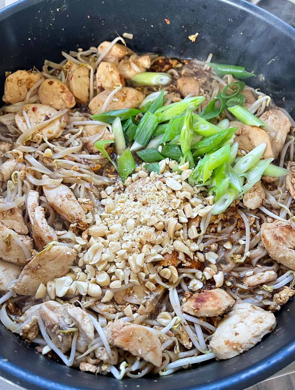 Chicken pad thai with chopped peanuts and spring onion in a pan.