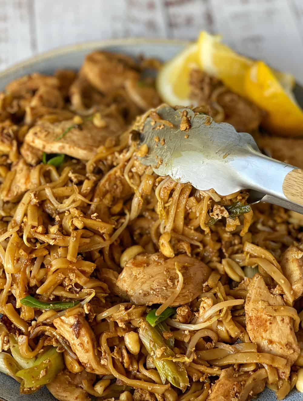 Chicken Pad Thai being served onto a plate with tongs.