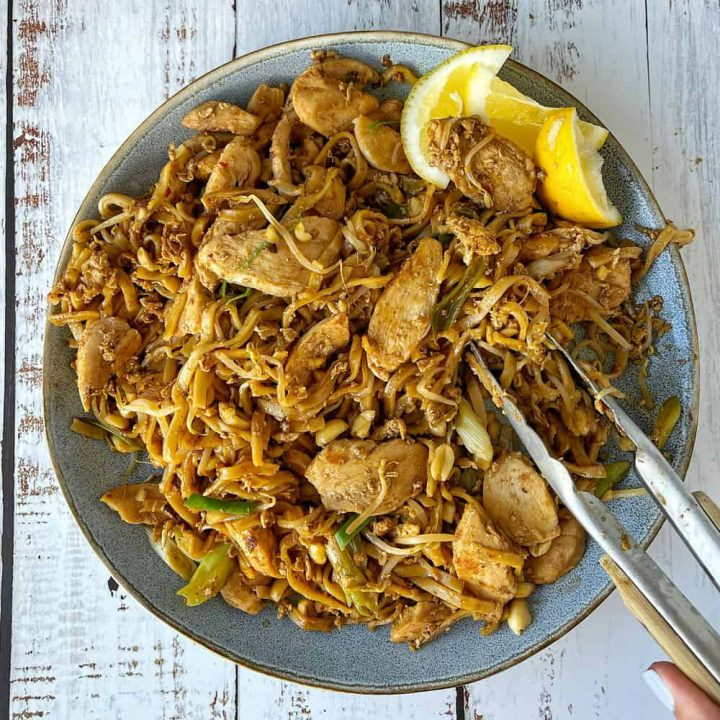 Chicken Pad Thai on a blue plate with tongs.