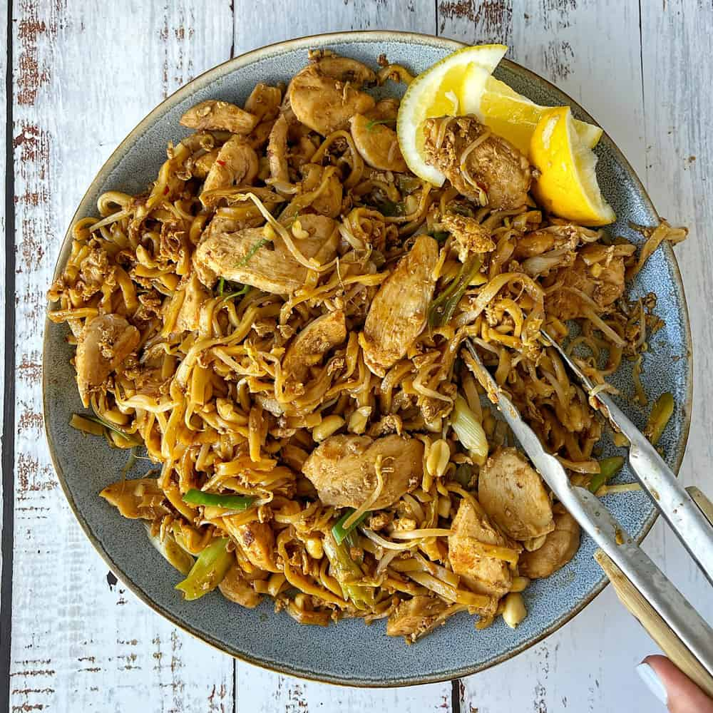 Chicken pad thai, lemon wedges and tongs in a blue bowl on a white table.