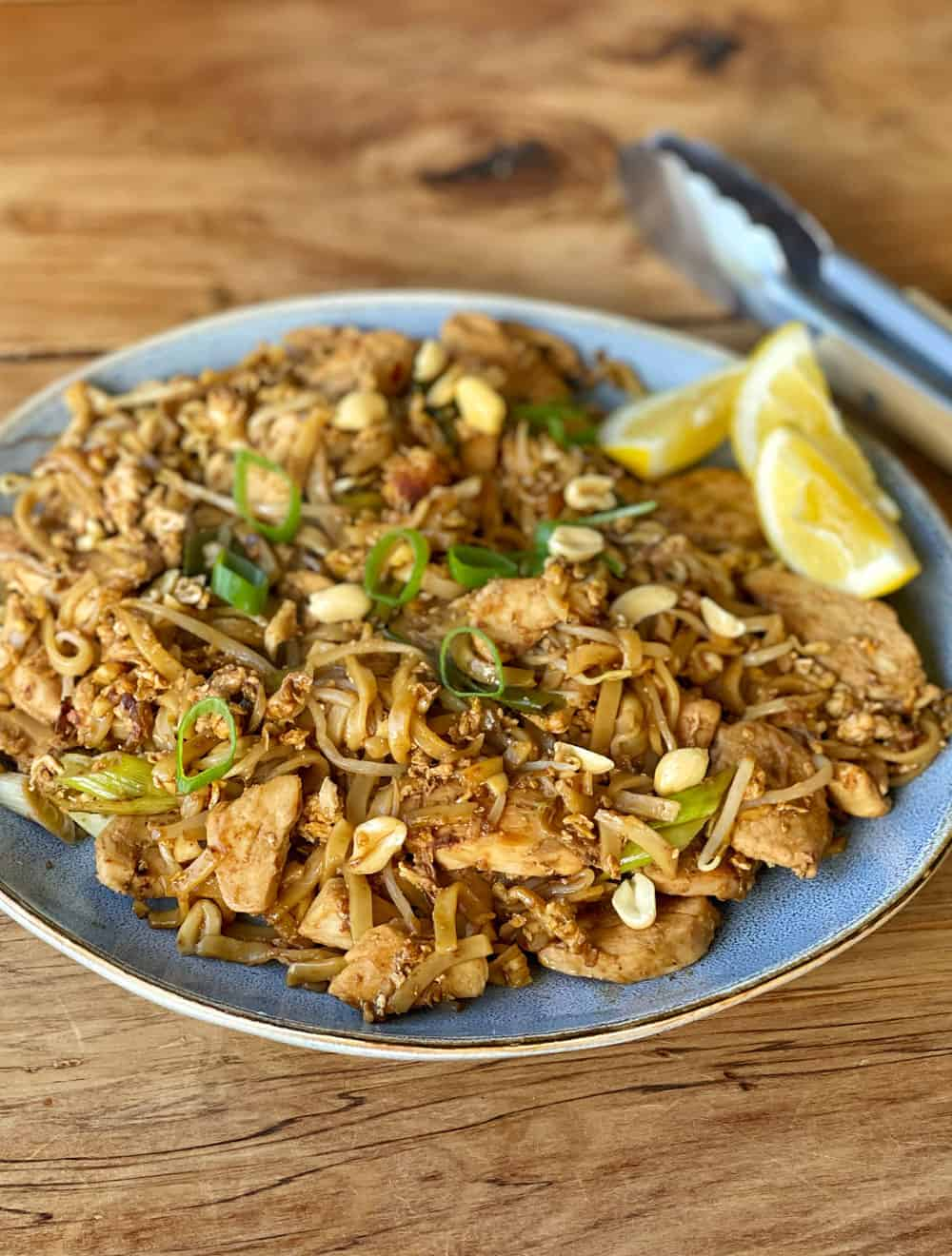 Chicken Pad Thai in a blue bowl on a wooden table.
