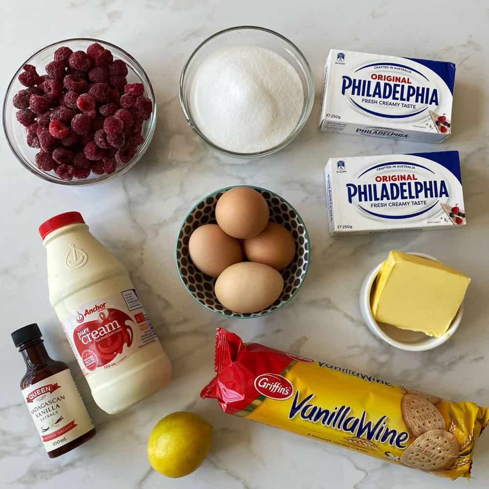 A bowl of frozen raspberries, a bowl of sugar, a bowl of eggs, 2 packets of cream cheese, butter, Vanilla Wine biscuits, a lemon, a bottle of cream and a bottle of vanilla essence on a grey and white tile.