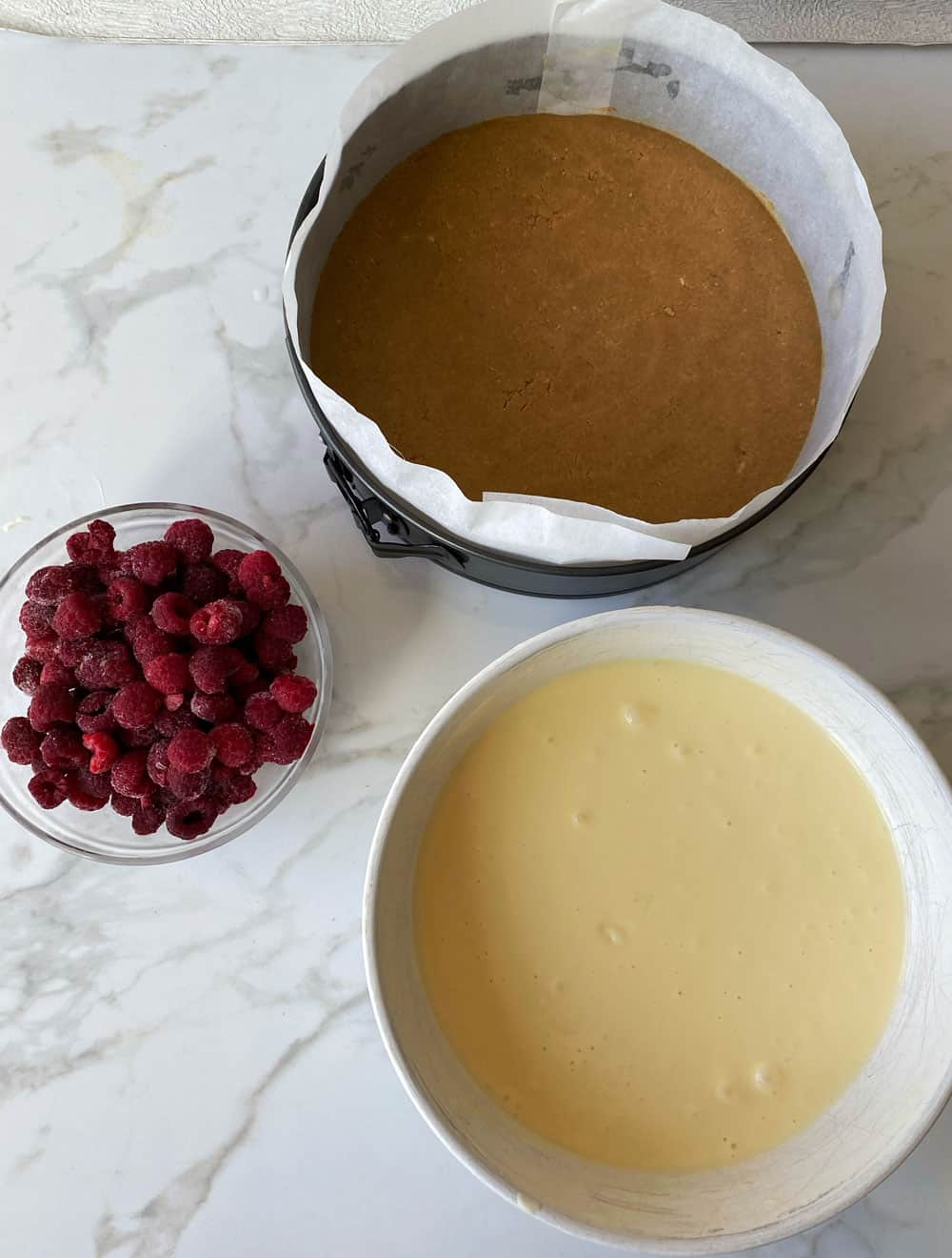 A bowl of frozen raspberries, a bowl of cream cheese mix and a lined cake tin sitting on a grey and white tile.