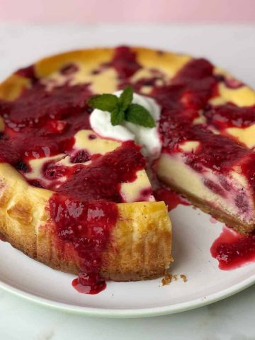 A close of a baked raspberry cheesecake on a white plate.