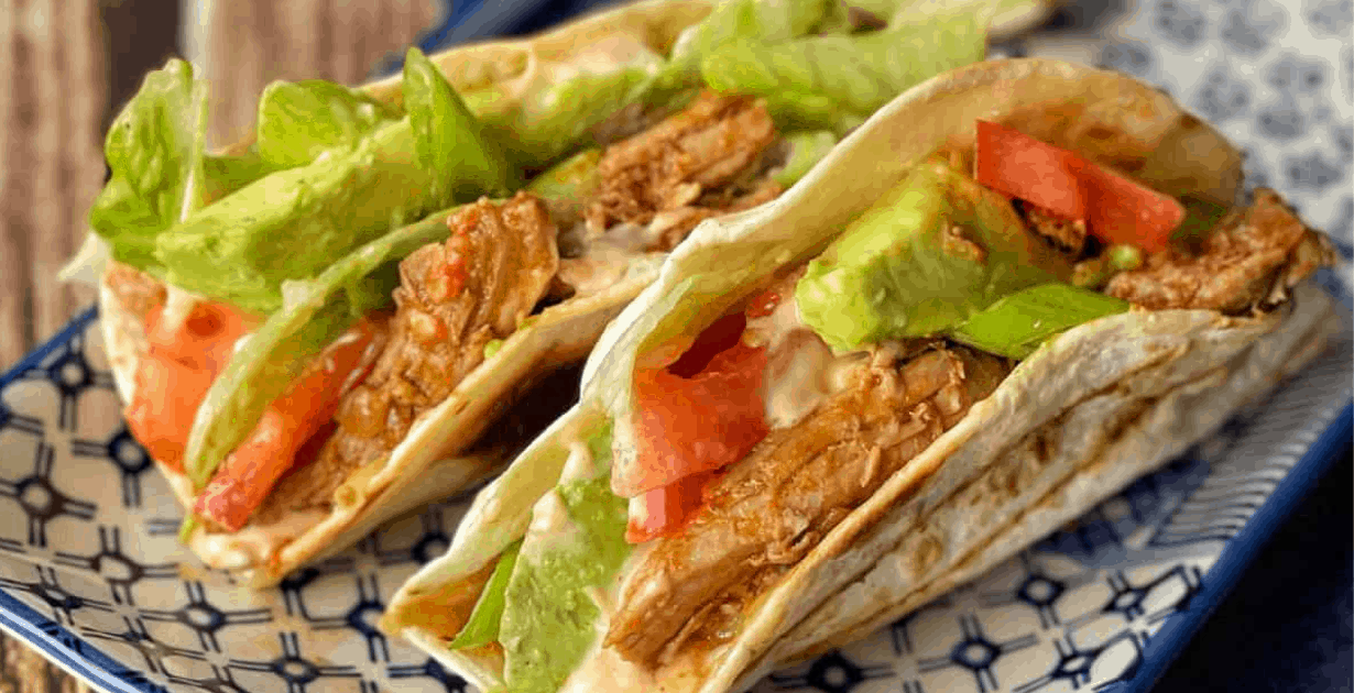 A close of up tortillas filled with pork and veg.