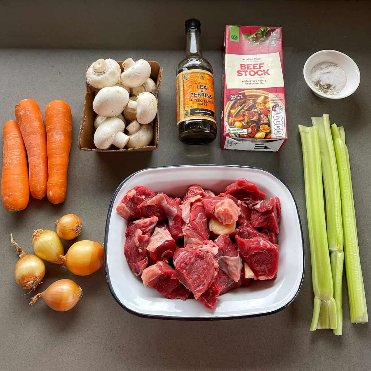 Ingredients for slow cooker beef stew on a grey bench.