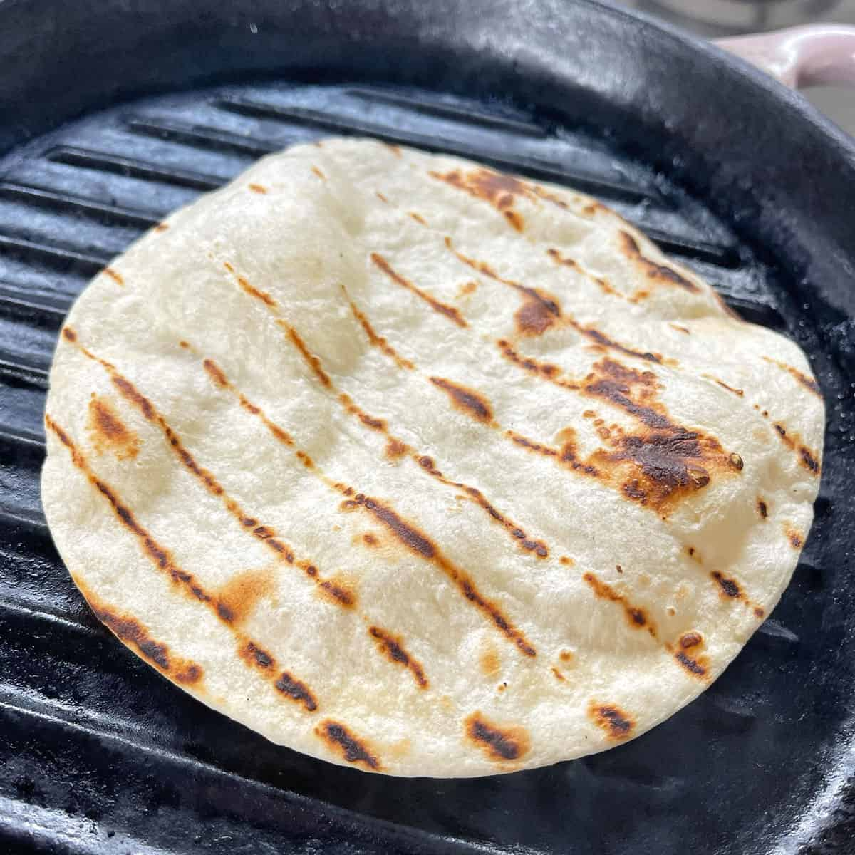 A tortilla toasting on a grill