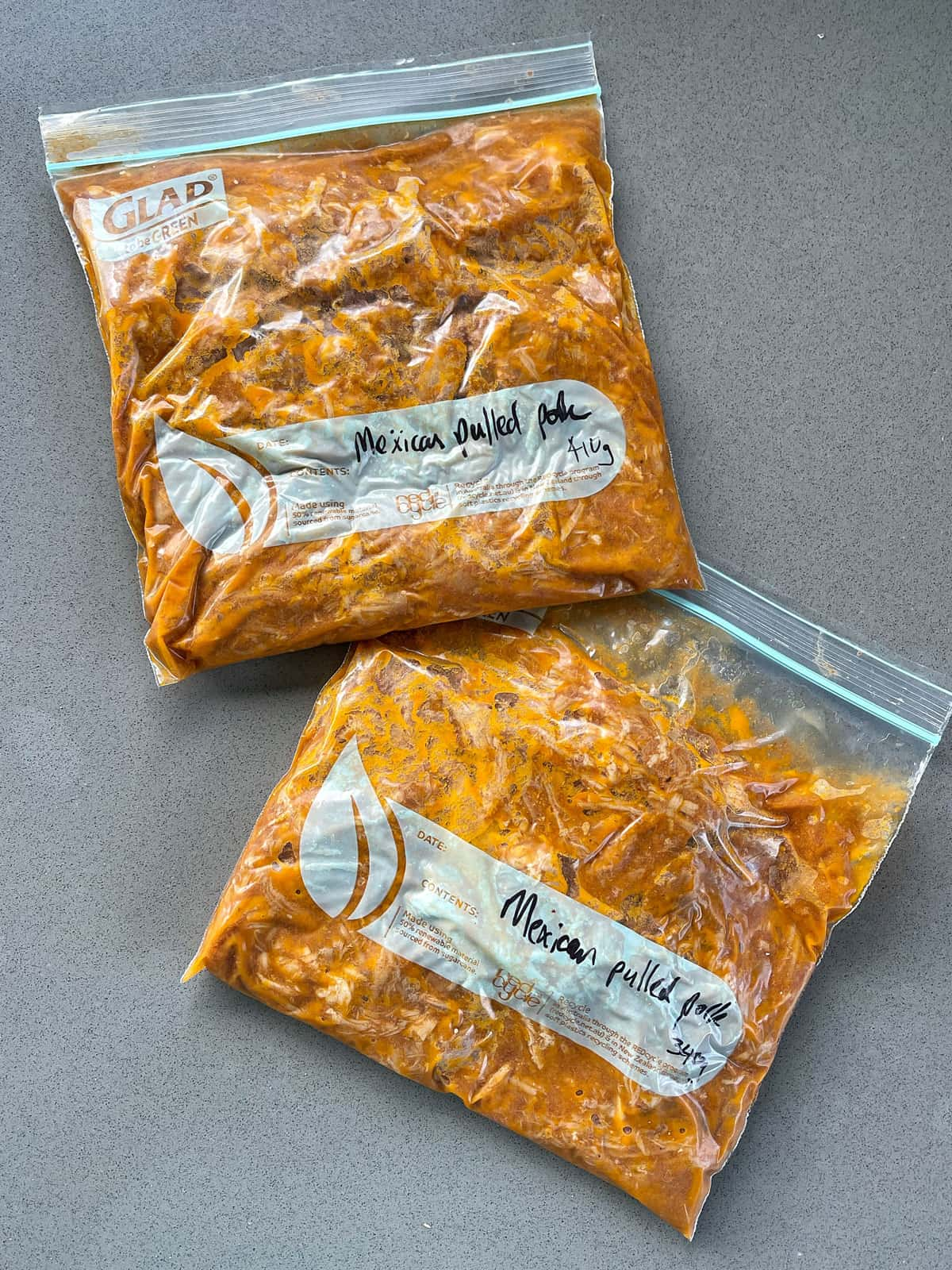 Two ziplock bags of Slow Cooker Mexican Pulled Pork on a grey bench.