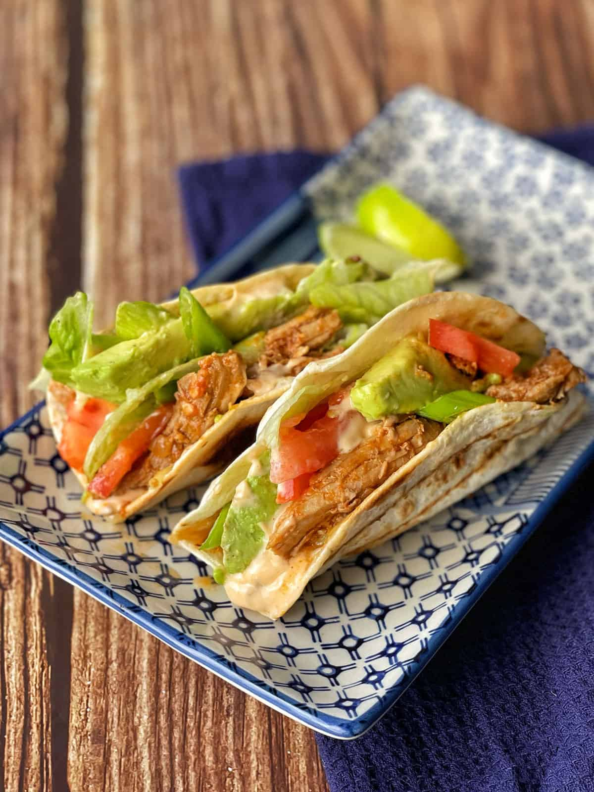 Two tortilla filled with pork and salad sitting on a white platter.