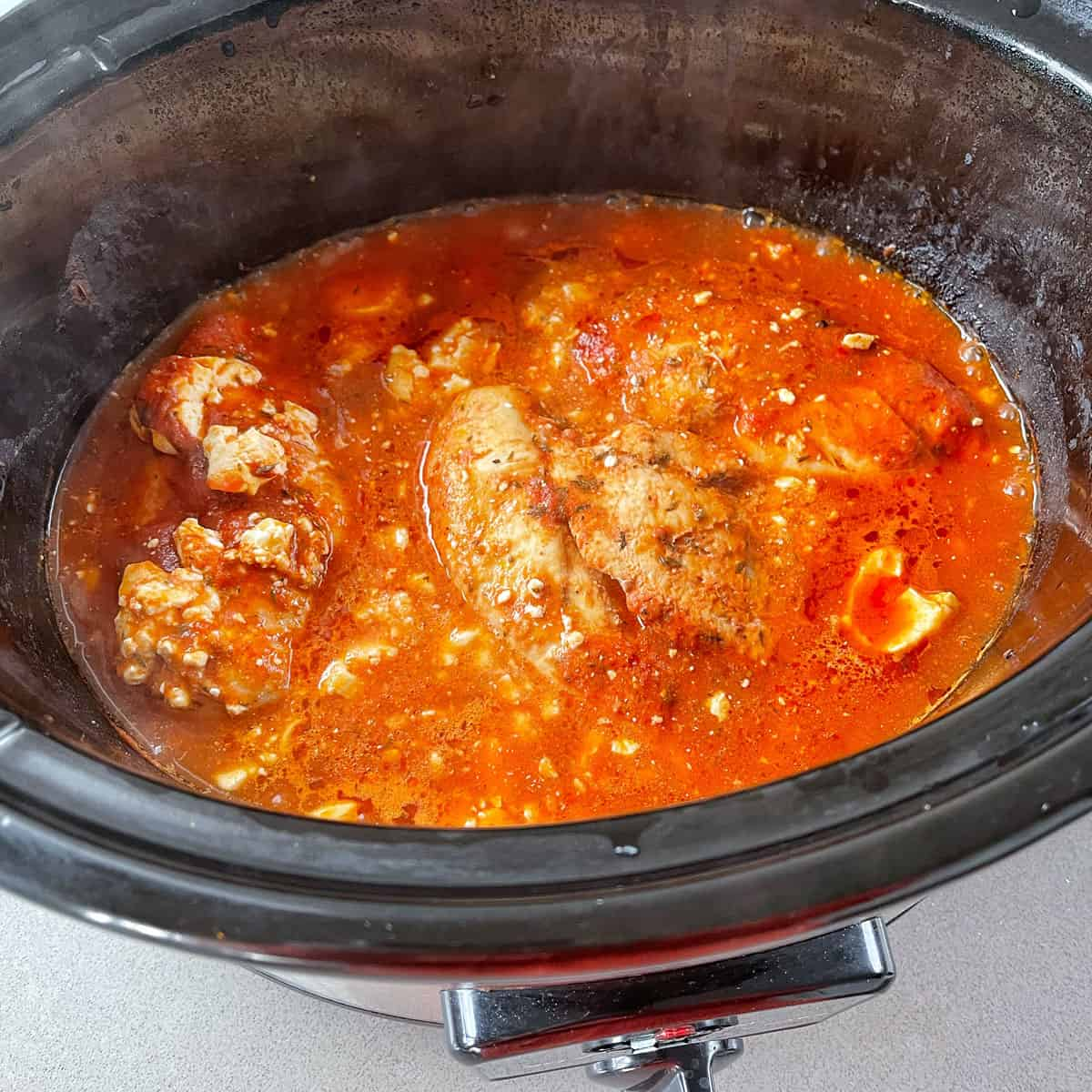 Shredded chicken cooking in the slow cooker