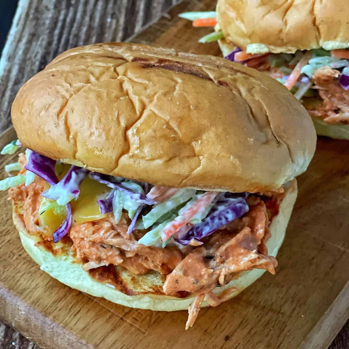 A close up of Slow Cooker Shredded Chicken in a burger bun.