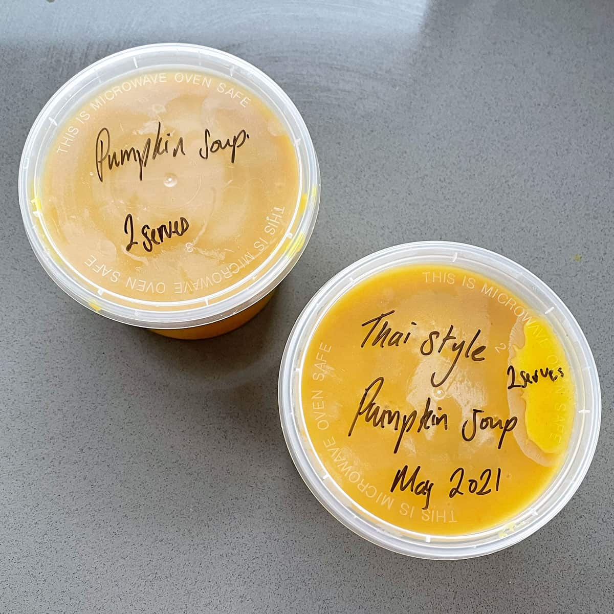 Two plastic containers of pumpkin soup sitting on a grey bench.