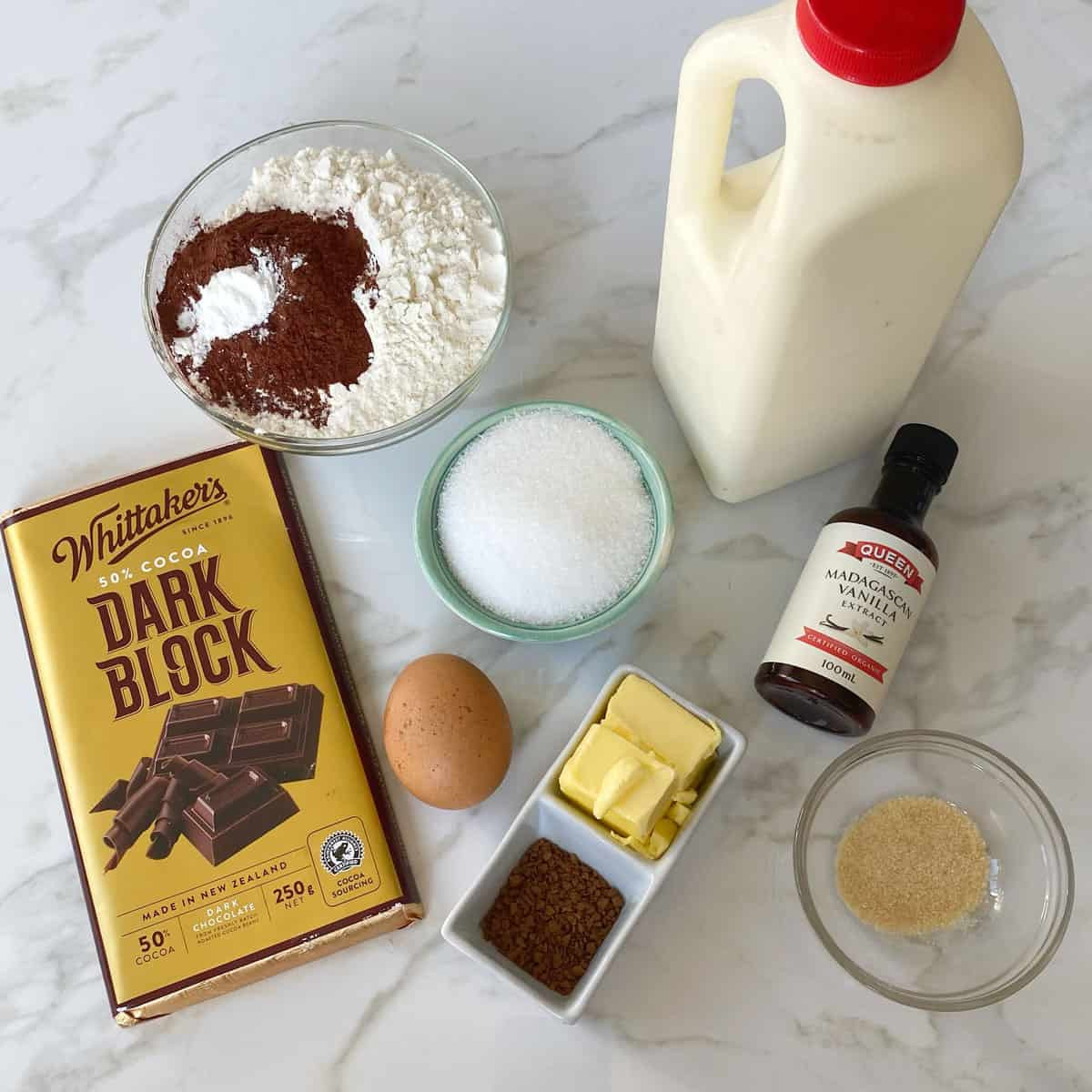 A block of chocolate, a bowl of flour and cocoa, cream, an egg, vanilla and butter arranged on a bench.