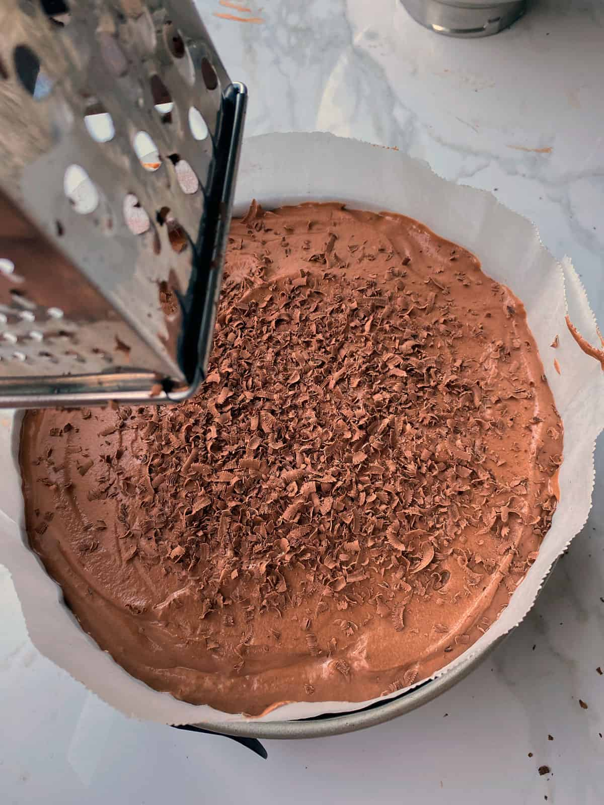Chocolate being grated onto the finished chocolate mousse cake in the lined tin.