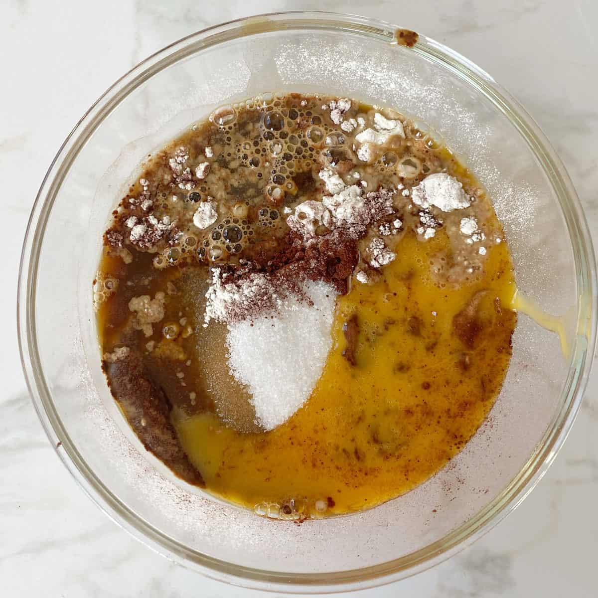 Dry ingredients and melted butter for Chocolate Mousse Cake in a glass bowl.