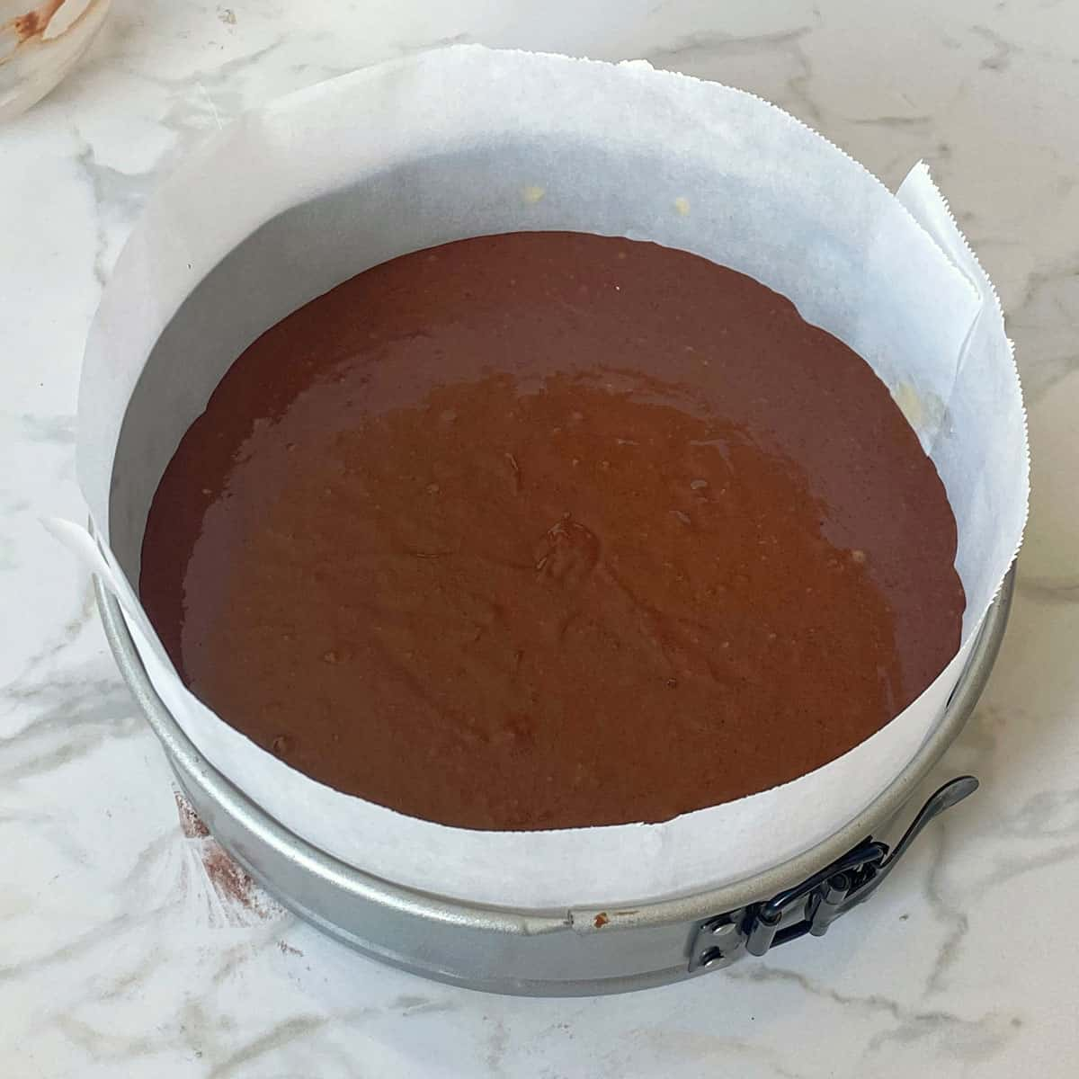Chocolate cake batter in a lined tin on a bench.