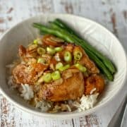 Apricot chicken served with rice and beans in a white bowl.