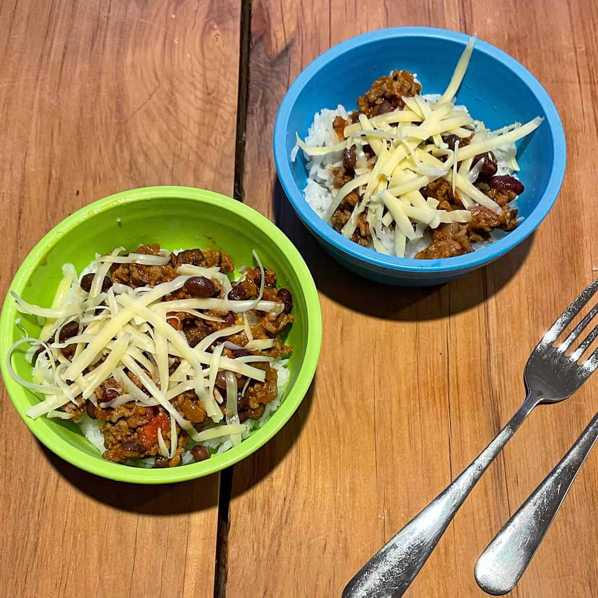 Kids' servings of chilli in a small green and blue bowl.