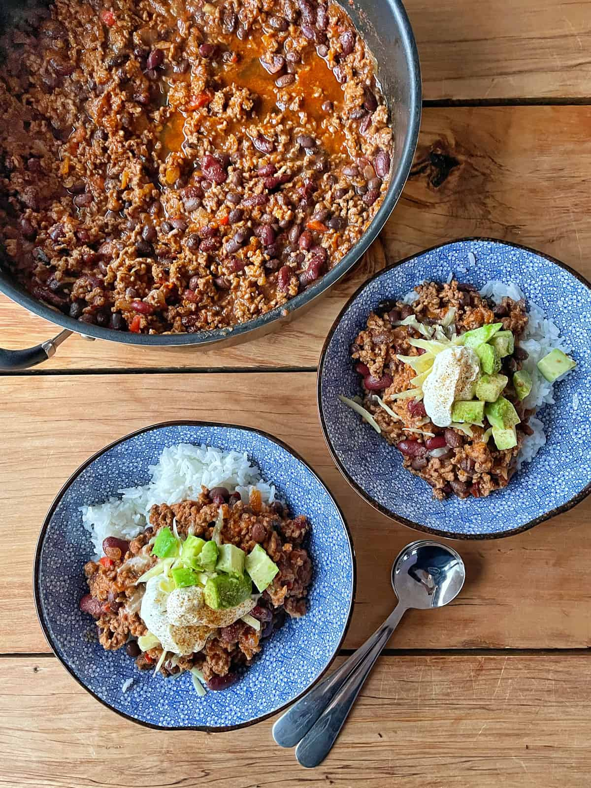 Chilli con carne in a large pot plus two small blue bowls of chilli on a wooden bench.