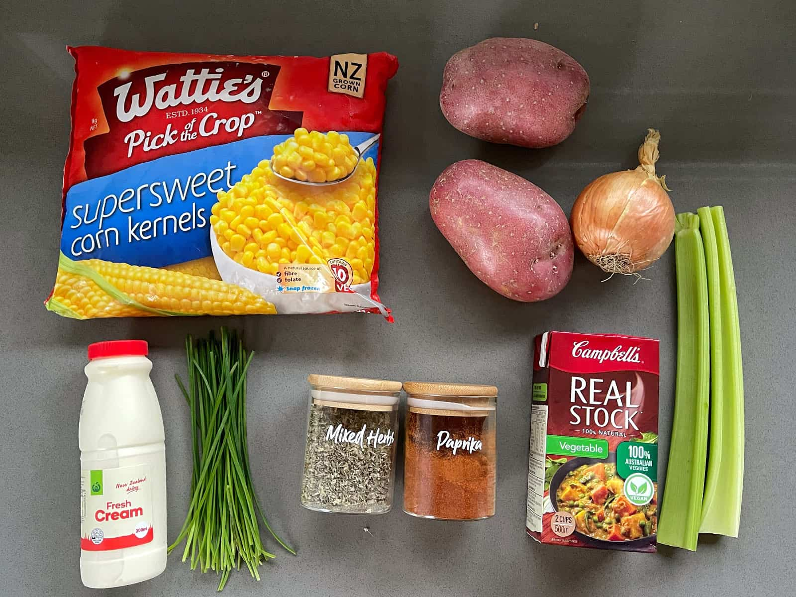 Ingredients for corn and potato chowder on a grey bench.