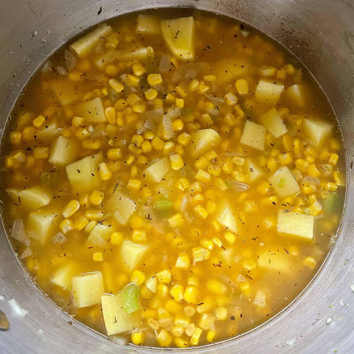 Corn and potato chowder cooking a large pot