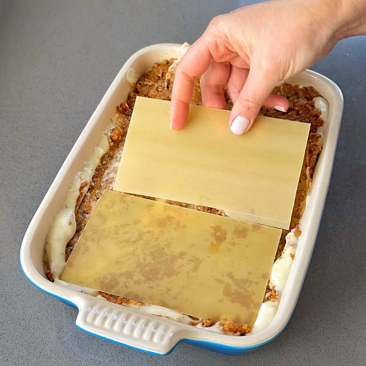 Layering up lasagne in a dish.