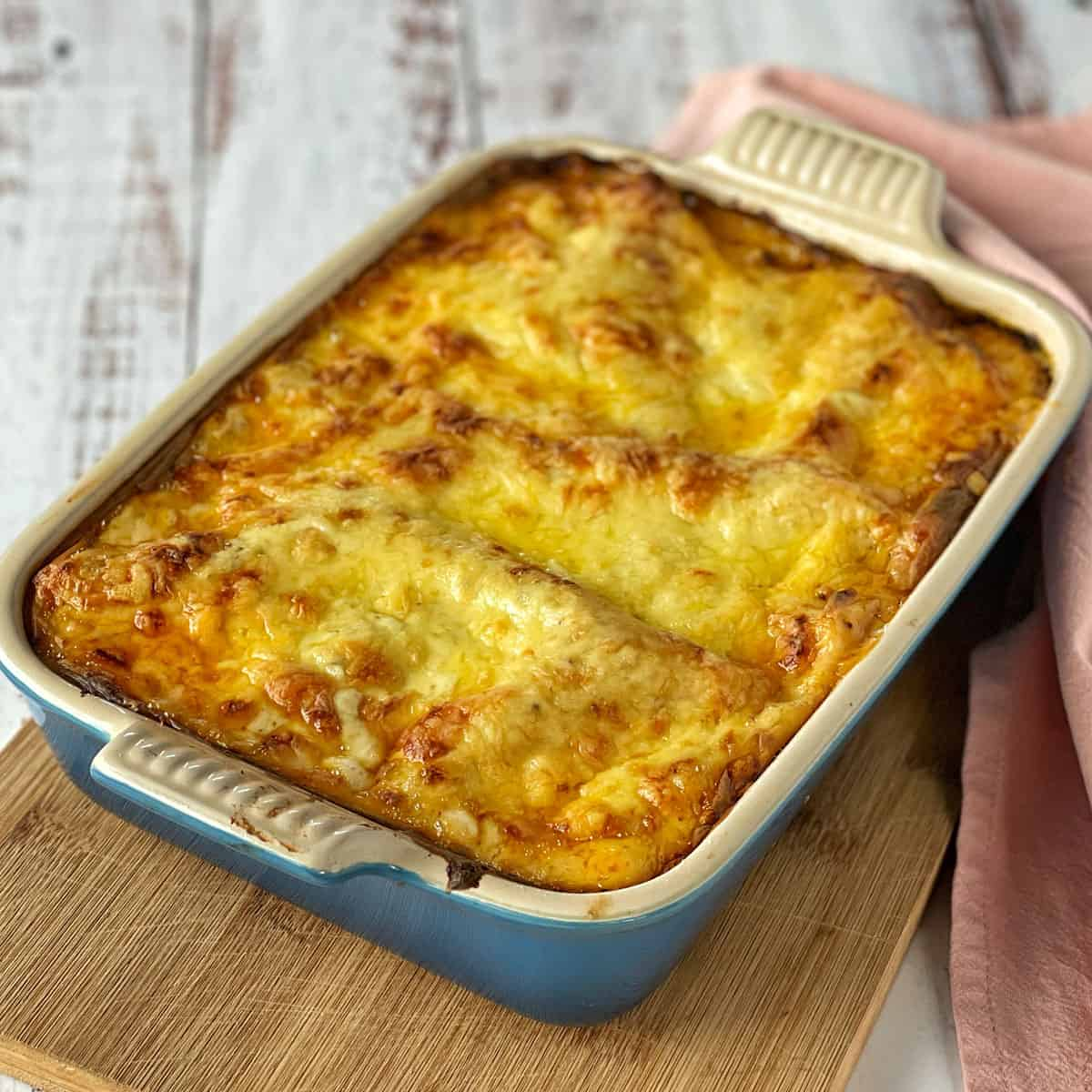 Cooked lasagne in a dish on a wooden board.
