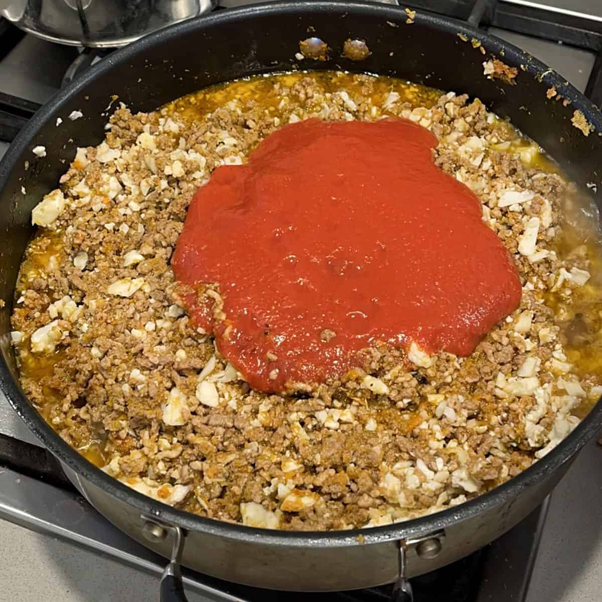 Mince and crushed tomatoes in a frying pan.