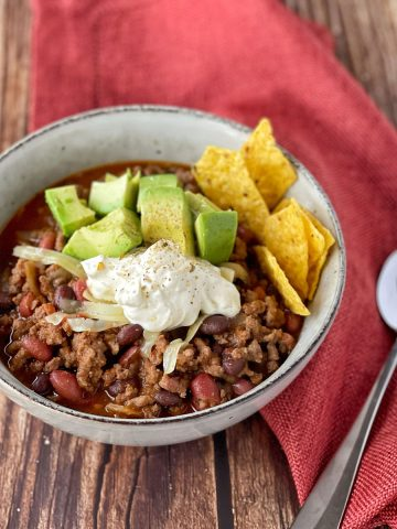 Chilli con carne served with avocado, sour cream and nacho chips in a white bowl.