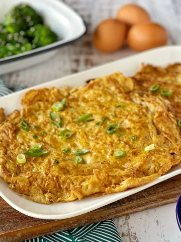 Egg Foo Young served on a white plate with steamed broccoli and fresh eggs in the background.